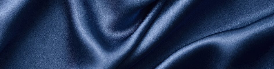 Silver silk background with a folds.  Abstract texture of rippled silk surface, wide long banner