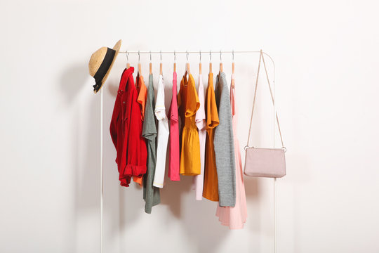 Fashionable clothes on hangers on a wardrobe rack on a light background.