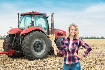 A young woman in a field on a background of a tractor with spike of wheat in her hands. Fotomurales
