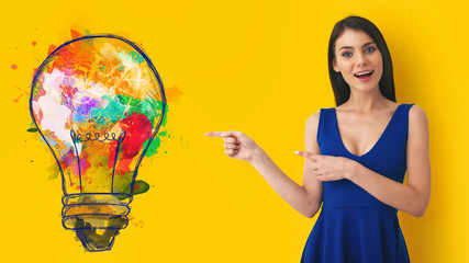 Wall Mural - Young woman pointing at big stylized light bulb on yellow background. Concept of idea and creativity