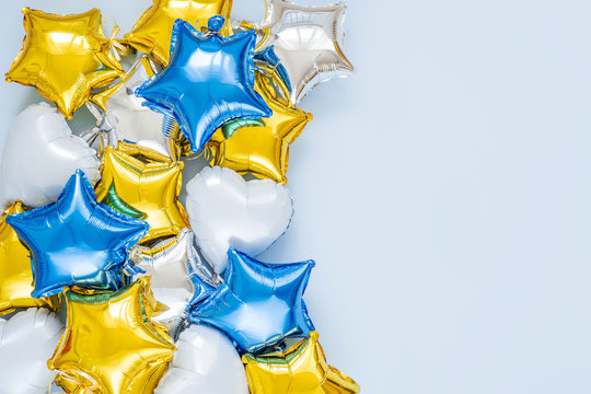 Gold and silver foil balloons of star shaped on blue background. Holiday and celebration concept. Birthday Day or party decoration. Metallic air balloons. Congratulation. Greeting card.