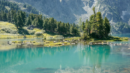 Wall Mural - Wild russian nature. Beautiful landscape with mirror emerald lake in the mountains. Clear turquoise water. Traveling in the Altai Republic. Tourism in Russia in the summer. Siberian lake reserve.