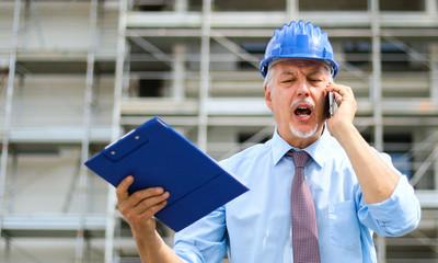 Angry senior engineer shouting at the phone