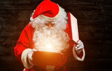 Santa Claus opening a gift box and being invested by a magical light
