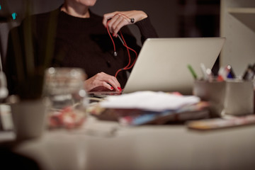 Woman with earphones and laptop.
