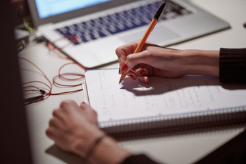 Woman writing in her notebook with pen.