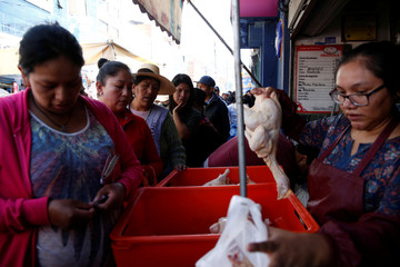 People line up to get chicken at a market in La Paz