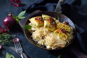 Gebratene schwäbische Gemüse-Maultaschen mit Röstzwiebeln auf Sauerkraut im Eisenpfandl  serviert - Fried Swabian vegetable ravioli with roasted onions served on sauerkraut in an iron frying pan