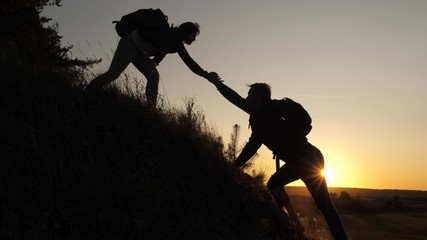 A male traveler holds out his hand to a female traveler climbing a hilltop. Tourists climb the mountain in the sunset, holding hands. teamwork of business people. Happy family on vacation.