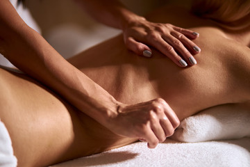Back of caucasian young female having aromatherapy massage with essential oil, deep tissue massage,...
