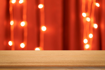 abstract blur dark red color curtain with LED lights in home interior background and aged wood perspective tabletop for show,ads,design product on display concept in merry xmas and happy new year