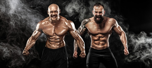 Sport and fitness concept. Two wild sportsmen boxers and bodybuilders posing on black background with smoke before competition or fight. Copy Space.