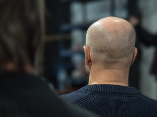 Back view of the man with a bald head in a conference hall.
