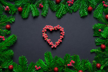 Christmas frame border wirh fir branch, berry heart and baubles on black background