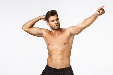 Sexy masculine man with six packs, standing bodybuilder pose naked torso white background, raising hand and pointing right, bragging how got fit in gym, got strong and handsome with exercises