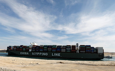 A container ship of China Shipping Line sails through the Suez Canal as Egypt celebrates the 150th anniversary of the canal opening in Ismailia