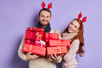 Romantic excited young couple posing over violet background with various gifts in red boxes, expressing happy feelings, looking straight, enjoying Christmas time, isolated, studio shot