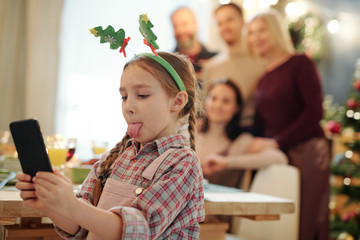 Little girl with Christmas headband on head showing tongue while making selfie