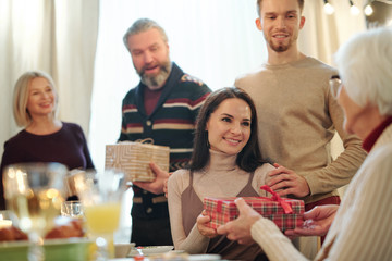 Young couple giving wrapped giftbox with Christmas present to granny