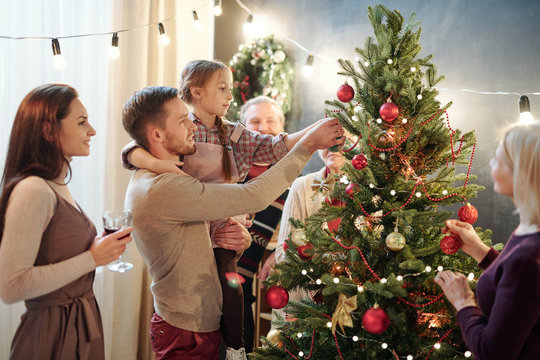Young man with his little daughter decorating Christmas tree at home