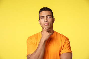 Attractive male entrepreneur start own business thinking about candidates, making choice, touch chin and looking away thoughtful, make serious face as decide, search idea in mind, yellow background