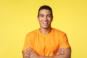 Joyful smiling handsome masculine man in t-shirt, cross arms chest confident, laughing as having carefree, relaxing conversation during party, standing yellow background upbeat, self-assured