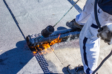 repair of bitumen roof with roll surfacing material with fire gas burner close-up, front and background blurred with bokeh effect