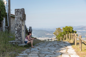Portrait of woman looking at the cellphone on her vacations in Galicia, viacrucis del Monte de Santa Tecla
