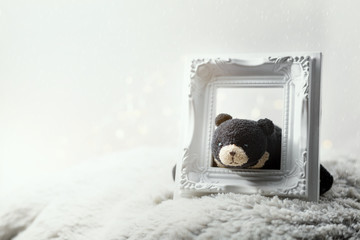 Lazy black bear holding empty picture frame.Merry Christmas concept background.