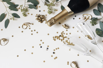 Happy New Year composition. Champagne glasses nad wine bottle with golden confetti stars and eucalyptus branches isolated on white table background. Celebration, party concept. Flat lay, top view.