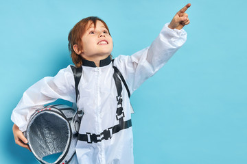 Caucasian child in white protective suit hold helmet in hands, surprisingly looking side at stars...