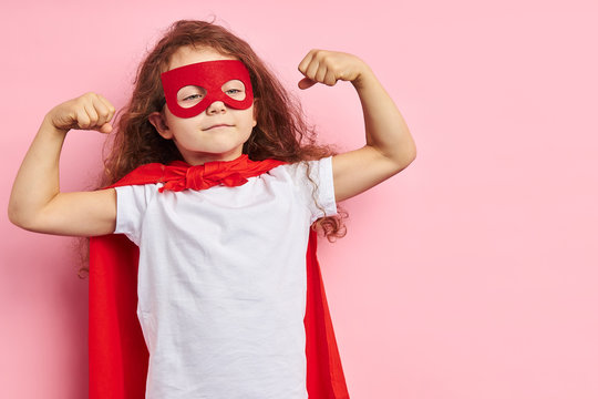 Beautiful little curly girl wearing red hero suit and mask showing how she is strong isolated over pink background