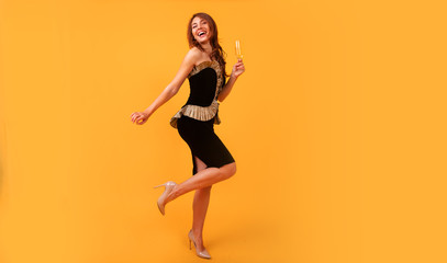 Full length image Young happy woman on yellow background drinking champagne, celebrating new year, wearing black dress, happy carnival disco party, sparkling confetti, holding glass, having fun.  Wall mural