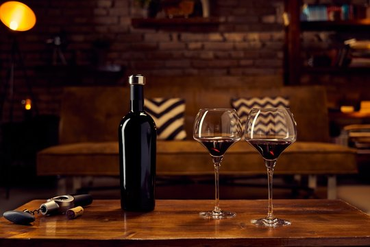 Glasses of red wine on table at home