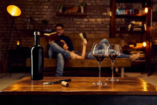 Glasses of red wine on table at home with couple