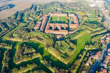 Aerial helicopter view of walls, moats, bastions, earthworks, outworks and barracks of modern six-star hexagon shaped renaissance fortress Cittadella of Alessandria on river Tanaro. Piedmont, Italy