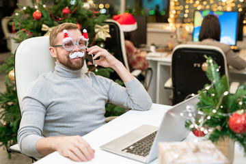 Happy young businessman in xmas eyeglasses phoning business partners