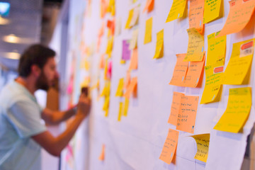 An agile software developer is updating Kanban board