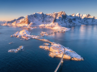Aerial view of small islands and bridge over the sea and snowy mountains in Lofoten Islands, Norway. Hamnoy at sunrise in winter. landscape with blue water, rocks, buildings, rorbu and road. Top view
