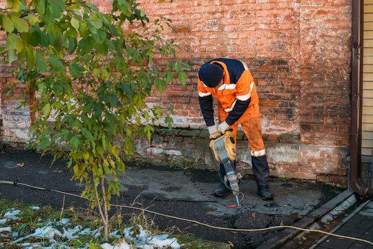 Road worker drilling asphalt on pavement with jackhammer