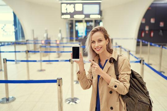 Travel and technology. Online check-in. Female traveler showing smartphone waiting for boarding near registration desk line.