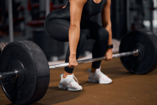 Close view of strong female hands trying to lift heavy metal barbell from light coloured floor, holding with effort, sport and health concept, side shot