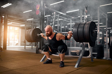 Sporty active man with strong arms and severe face, trying to stand with heavy barbell on hands, strong powerlifter training in gym, white smoke in the air, side indoor shot