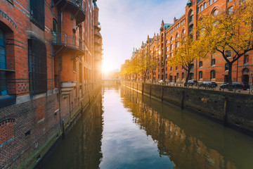 Speicherstadt warehouse district in Hamburg, Germany. Autumn season weather. Old brick buildings, river channel of Hafencity quarter with sunset golden flares and water reflections