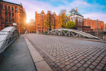 Arch bridge over canals with cobbled road in the Speicherstadt of Hamburg, Germany, Europe. Historical red brick building lit by golden sunset light near water castle palace