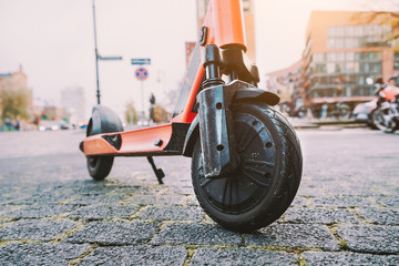 Lilac e-scooter front wheel tire perspective parked outdoor on pavement of urban city scene. Hamburg, Germany, Europe