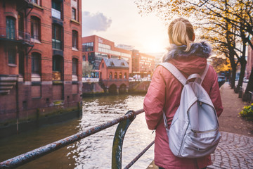 Back rear view of adult woman tourist with backpack enjoying autumn beautiful sunset scene on the Speicherstadt historic warehouse district in Hamburg, Germany, Europe
