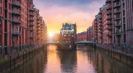 Hamburg city old port, Germany, Europe. Historical famous warehouse district with water castle palace at sunset golden light. Panoramic picture scene