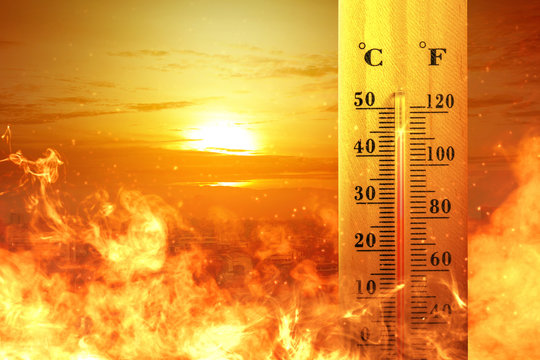 Thermometer with high temperature on the city with glowing sun background