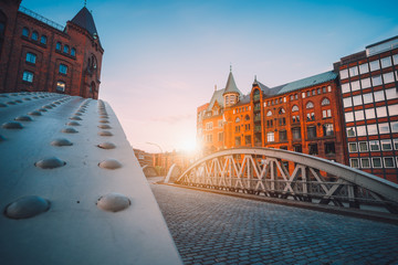 Iron arch bridges in historical warehouses in Speicherstad district in Hamburg, Germany. Backlit sun light flares